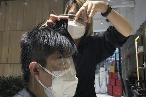 A barber wearing a protective face mask cuts a clients hair with an eye cover and face mask at a hair salon in Beijing, Monday, Feb. 24, 2020. Monday is the second day of the second month of the Chinese lunar calendar, traditionally an auspicious time when people rush into barbershops to get new haircuts. Getting a fresh look on the day is thought to bring good luck for the year ahead, but getting a haircut has become a challenge in China now that most barbershops are temporarily shut to avoid public gatherings amid the virus outbreak. (AP Photo/Olivia Zhang)