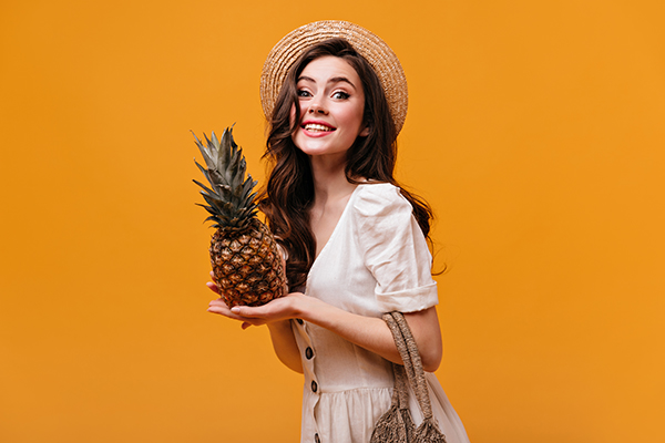 Pretty woman in cotton dress looks into camera with smile and poses with pineapple on isolated background